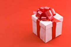 Contenitore di regalo bianco con l'arco rosso del nastro del raso Immagini Stock