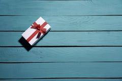 Contenitore di regalo bianco con l'arco rosso sulle plance di legno blu immagine stock
