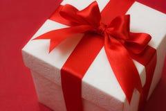Contenitore di regalo bianco con un nastro rosso ed arco su Ba rosso Fotografia Stock Libera da Diritti