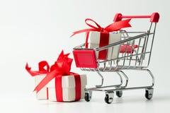 Contenitore di regalo bianco legato con il nastro rosso in un carrello fotografie stock