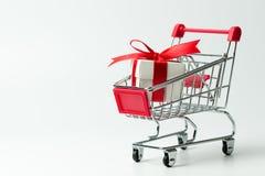Contenitore di regalo bianco legato con il nastro rosso in un carrello immagini stock