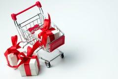 Contenitore di regalo bianco legato con il nastro rosso in un carrello fotografie stock libere da diritti