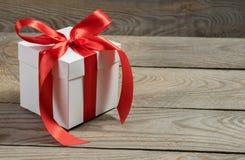 Contenitore di regalo bianco su fondo di legno Immagine Stock