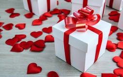 Contenitore di regalo bianco sui precedenti delle forme del tessuto di cuori Immagini Stock