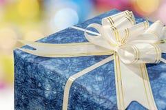 Contenitore di regalo blu con il nastro e l'arco bianchi e dorati Immagini Stock
