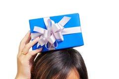 Contenitore di regalo blu del posto asiatico della donna sopra la sua testa Fotografie Stock