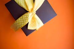 Contenitore di regalo di Brown con il nastro giallo su fondo arancio Vista superiore con lo spazio della copia immagini stock