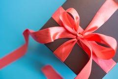 Contenitore di regalo di Brown con il nastro rosso su fondo blu Vista superiore con lo spazio della copia fotografie stock