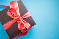 Contenitore di regalo di Brown con il nastro rosso su fondo blu Vista superiore con lo spazio della copia fotografie stock libere da diritti