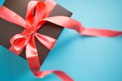Contenitore di regalo di Brown con il nastro rosso su fondo blu Vista superiore con lo spazio della copia fotografia stock