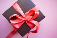 Contenitore di regalo di Brown con il nastro rosso su fondo rosa Vista superiore con lo spazio della copia fotografia stock libera da diritti