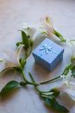 Contenitore di regalo circondato con i fiori di alstroemeria sulla superficie del marmo Immagine Stock Libera da Diritti