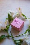 Contenitore di regalo circondato con i fiori di alstroemeria sulla superficie del marmo Fotografia Stock