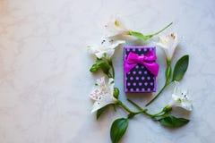 Contenitore di regalo circondato con i fiori di alstroemeria sulla superficie del marmo Fotografia Stock Libera da Diritti