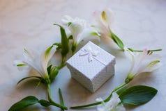 Contenitore di regalo circondato con i fiori di alstroemeria sulla superficie del marmo Immagini Stock Libere da Diritti