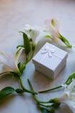 Contenitore di regalo circondato con i fiori di alstroemeria sulla superficie del marmo Immagini Stock