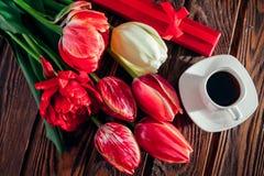 Contenitore di regalo con caffè ed i tulipani freschi su fondo di legno Sorpresa di mattina Scena antiquata di mattina: macchina  immagini stock