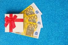 Contenitore di regalo con 200 euro su fondo blu scintillante luminoso e festivo Fotografie Stock Libere da Diritti