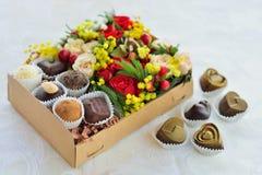 Contenitore di regalo con i fiori e le caramelle fatti di cioccolato Fotografia Stock