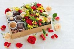 Contenitore di regalo con i fiori e le caramelle fatti di cioccolato Immagine Stock