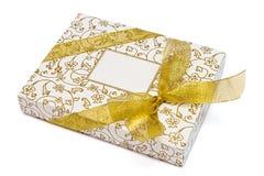 Contenitore di regalo con il nastro dell'oro ed arco su bianco Fotografia Stock