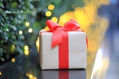 Contenitore di regalo con il nastro rosso su luce dorata con il BAC dell'estratto del bokeh immagine stock