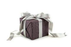 Contenitore di regalo con l'arco d'argento isolato su fondo bianco Fotografia Stock
