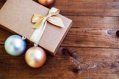 Contenitore di regalo con l'arco dell'oro con le palle di hristmas su fondo di legno Fotografia Stock