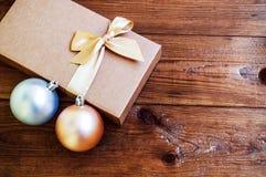 Contenitore di regalo con l'arco dell'oro con le palle di hristmas su fondo di legno Fotografia Stock Libera da Diritti