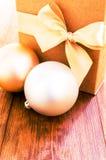 Contenitore di regalo con l'arco dell'oro con le palle di hristmas su fondo di legno Fotografie Stock Libere da Diritti