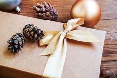 Contenitore di regalo con l'arco dell'oro con le palle di natale ed abete rosso del cono su w Fotografie Stock