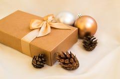 Contenitore di regalo con l'arco dell'oro con le palle di natale ed abete rosso del cono su w Fotografia Stock
