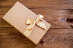 Contenitore di regalo con l'arco dell'oro su fondo di legno Fotografia Stock Libera da Diritti