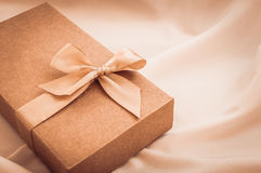 Contenitore di regalo con l'arco dell'oro sul fondo bianco del panno Immagine Stock Libera da Diritti