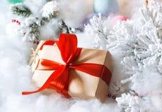 Contenitore di regalo con l'arco ed i giocattoli rossi dell'albero di Natale ed imitazione della neve immagini stock libere da diritti