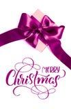 Contenitore di regalo con l'arco porpora su un fondo bianco e su un Buon Natale del testo Calligrafia dell'iscrizione Immagine Stock Libera da Diritti