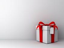 Contenitore di regalo con l'arco rosso del nastro ed etichetta in bianco sul fondo bianco vuoto della parete Immagine Stock