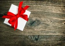 Contenitore di regalo con l'arco rosso del nastro sopra fondo di legno rustico Immagini Stock Libere da Diritti