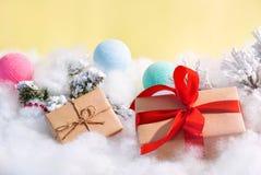 Contenitore di regalo con l'arco rosso e fondo giallo e giocattoli colorati di natale fotografia stock libera da diritti