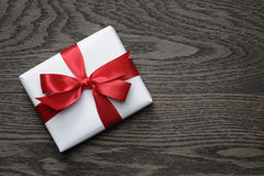 Contenitore di regalo con l'arco rosso sulla tavola di legno Fotografia Stock Libera da Diritti