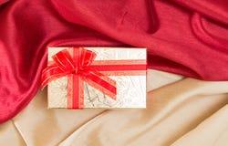 Contenitore di regalo con l'arco, sui tessuti ondulati rossi e dorati Fotografie Stock Libere da Diritti