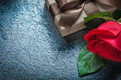 Contenitore di regalo con la rosa rossa marrone dell'arco sulle feste nere co del fondo Fotografia Stock