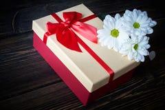Contenitore di regalo con le margherite bianche su fondo di legno Fotografie Stock Libere da Diritti