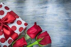 Contenitore di regalo con le rose rosse dell'arco sul concetto di feste del bordo di legno Fotografie Stock