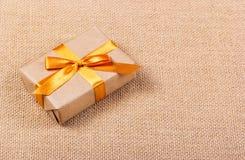 Contenitore di regalo con un arco dorato Feste e sorprese Immagine Stock
