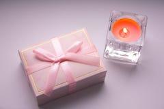 Contenitore di regalo con un arco e una candela accesa immagini stock libere da diritti
