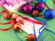 Contenitore di regalo con un nastro rosso e le palle del nuovo anno Immagini Stock