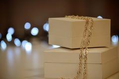 Contenitore di regalo con una catena dell'oro su un fondo delle luci Immagini Stock Libere da Diritti