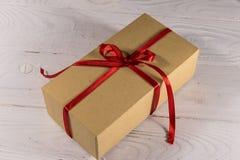 Contenitore di regalo del cartone con il nastro rosso sulla tavola di legno bianca Immagini Stock Libere da Diritti
