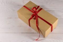 Contenitore di regalo del cartone con il nastro rosso sulla tavola di legno bianca Immagine Stock Libera da Diritti